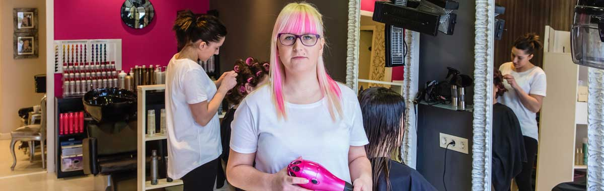 Image of a hairdresser, with pink hair, standing in her salon, illustrating that hairdressers are typical customers of GK Taxation Services